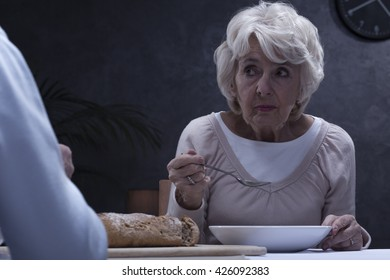 Shot of a senior woman eating soup and looking at her husband