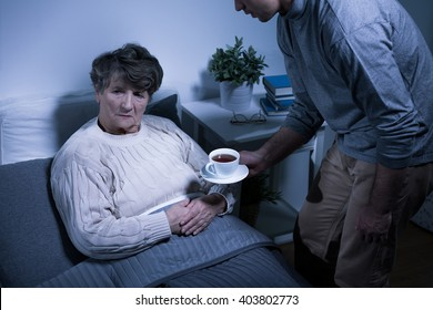 Shot of an senior woman refusing to take a cup of tea from her grandson
