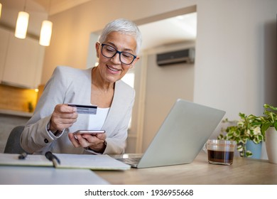 Shot of a senior woman using a credit and mobile while working on her finances at home. Senior woman shopping online. Happy senior woman making online payments of bill using laptop.