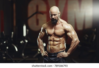 Shot of a serious mature male bodybuilder posing shirtless at the gym looking to the camera. Handsome mature athlete posing shirtless showing off his muscular perfect torso