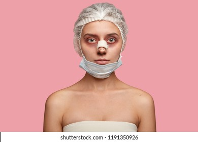 Shot of serious woman wears medical hat and mask, has rhinoplasty, preapres for blepharoplasty, has bruises around eyes, looks seriously at camera, poses against pink background. Beauty treatments