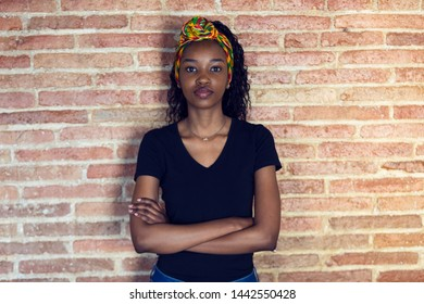 Shot of serious young woman looking at camera with arms crossed while standing in front of a wall.
