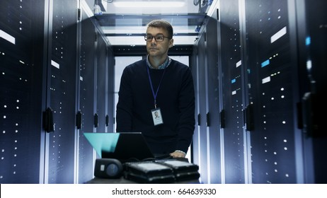 Shot of Server Engineer Pushing Crash Cart with Laptop, Hard Drives and Hardware Through Data Center. He Walks along Rows of Server Racks.