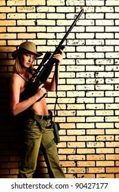 Shot of a sexy woman soldier posing against brick wall.