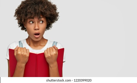 Shot of shocked schoolgirl has curly hair, openes mouth from surprise, holds textbook, realizes day of exam is coming, poses against white background with free space for your advertisement, promotion