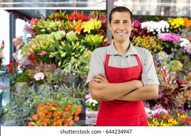 Shot of a shop man with crossed arms in a garden shop with plants and flowers
