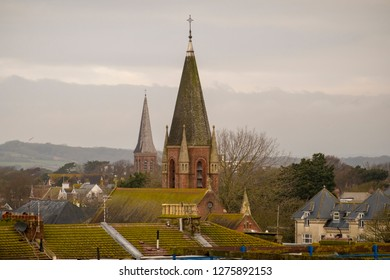 Shot showing various rooftops and church spire in worthing west susserx and the south downs on a misty day.
