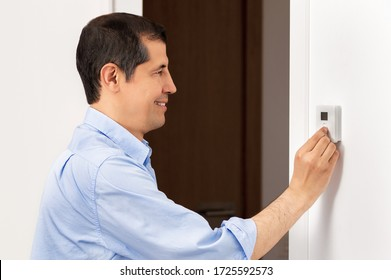 Shot of a side view portrait of a beautiful happy business man push button digital thermostat at house