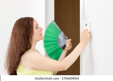 Shot of a side view portrait of a sad woman push button digital thermostat and refreshing with a fan at living room at home