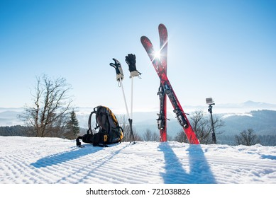 Shot of skiing equipment - skis, backpack, sticks, gloves and action camera on monopod, on top of the ski slope at ski resort in the mountains winter sports lifestyle extreme active concept