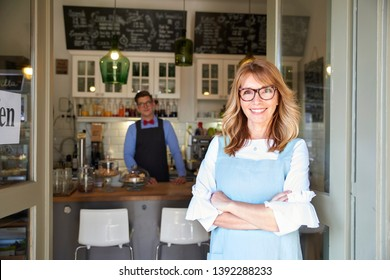 Shot of small cafe owner woman standing at coffee shop door and waiting for guest while young barista standing behind her at the counter. Family business.
