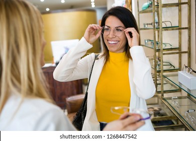 Shot of smiling beautiful woman choosing and showing eyeglasses to attractive young oculist in optic shop.