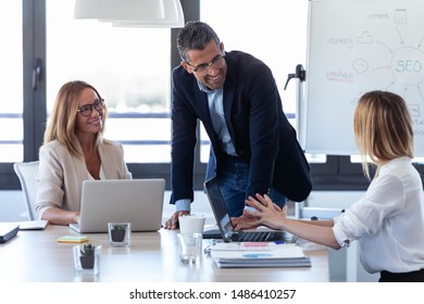 Shot of smiling businessman talking with colleagues in the meeting on coworking space.