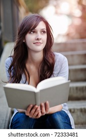 A shot of a smiling college student reading a book