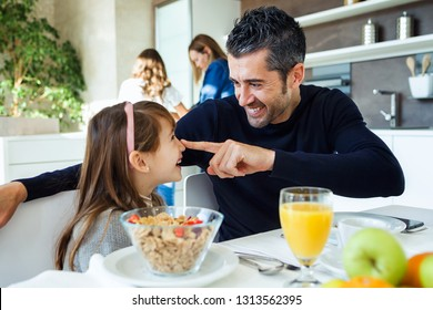 Shot of smiling cute father and daughter having fun while having breakfast in family in the kitchen at home.