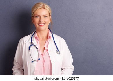 Shot of smiling female doctor wearing medical gown while standing at grey background with copy space.