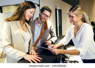 Shot of smiling female receptionist giving information with digital tablet to two young entrepreneurs in advertising agency.