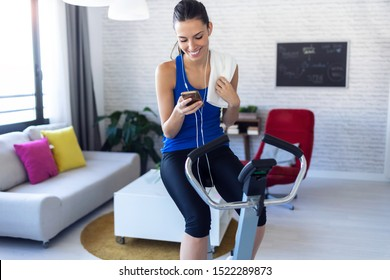 Shot of smiling fitness girl using mobile phone after training on exercise bike at home.