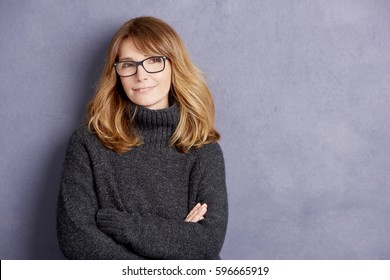Shot of a smiling mature woman with arms folded standing at grey wall.