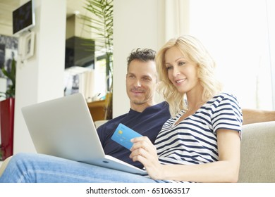 Shot of a smiling middle aged couple sitting on couch and using credit card and laptop while shopping online.