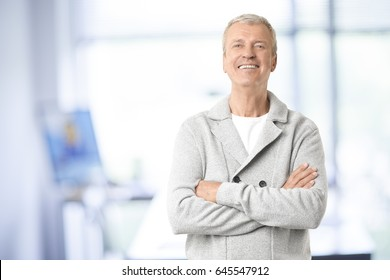 Shot of a smiling senior businessman standing with arms crossed in the office.