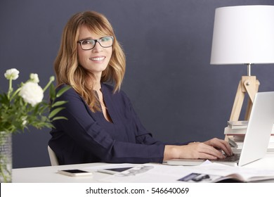 Shot of smiling woman typing in laptop while working on new project at her home office.
