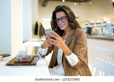 Shot of smiling young businesswoman with eyeglasses texting with her mobile phone in the coffee shop.