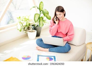 Ich wollte lächelnde junge Geschäftsfrau, die mit jemandem auf ihrem Handy spricht und Laptop benutzt, während sie von zu Hause aus arbeitet. Heimbüro.
