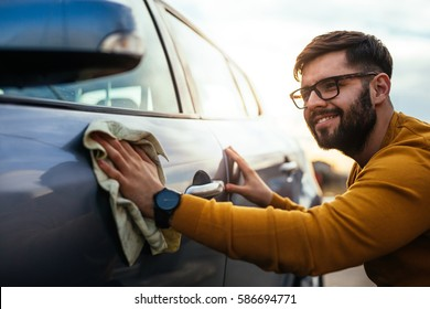Shot of a smiling young man polishing his car with a cloth.