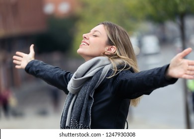 Shot of smiling young woman breathing fresh air and raising arms in the city.