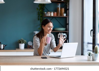 Shot of smiling young woman waving through the laptop web camera while holding a cup of coffee in the kitchen at home.