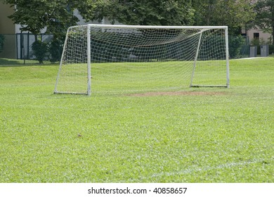 A shot of a soccer goal at the end of a empty field at a park.