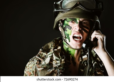 Shot of a soldier talking by radio station. Studio shot over black background.