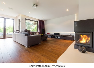 Shot of a spacious modern living room with big grey sofas and a fireplace