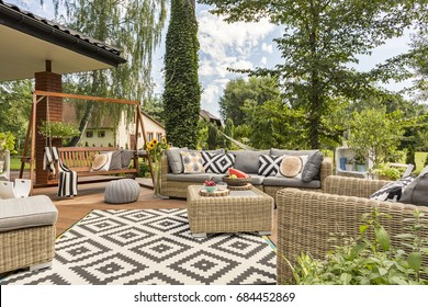 Shot of spacious terrace with cosy garden furniture and a carpet with mosaic theme
