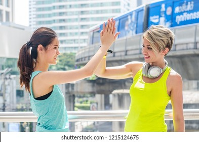 Shot of sport womens friends giving high-five at street city. Professional sport shaking hands after the game.