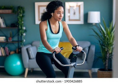 Shot of sporty african young woman exercising on smart stationary bike and listening to music at home.