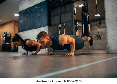 Shot of a sporty young couple doing pushups at the gym