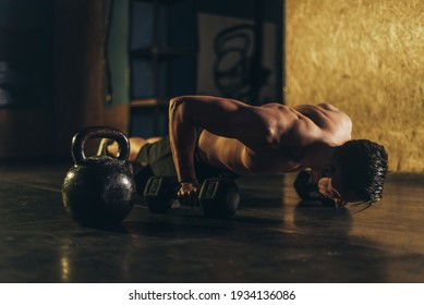 Shot of a sporty young shirtless man doing pushups on the dumbbell in the gym
