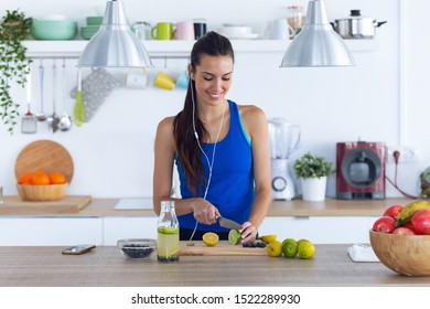 Shot of sporty young woman cutting limes while listening to music in the kitchen at home.
