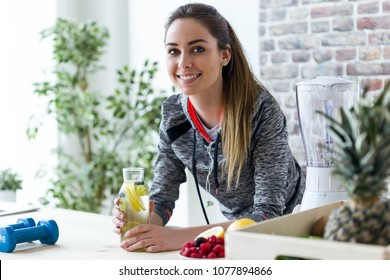 Shot of sporty young woman looking at camera while drinking lemon juice in the kitchen at home.