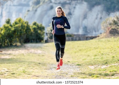 Shot of sporty young woman running on mountain in beautiful nature.