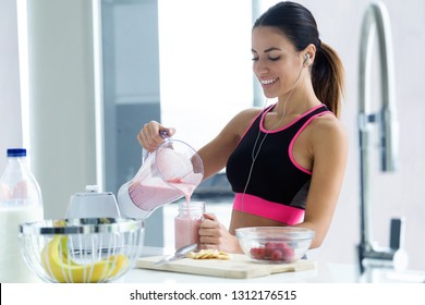 Shot of sporty young woman serving strawberry smoothie in a glass jar in the kitchen at home.