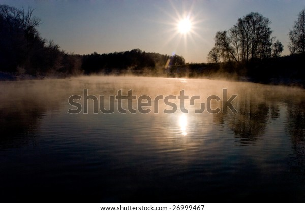 Shot of spring foggy river surrounded by trees with bright sun shining above