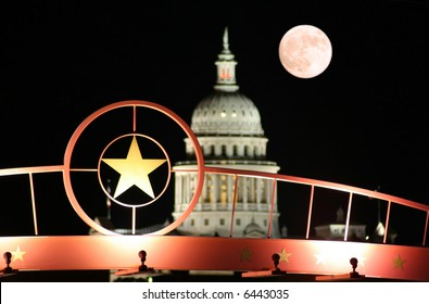 A shot of the star of Texas with the Texas State Capitol Building and the moon in the background.