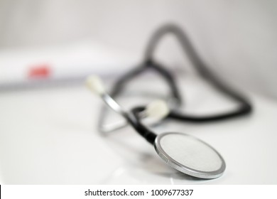 Shot of Stethoscope and Spiral notebook on white table