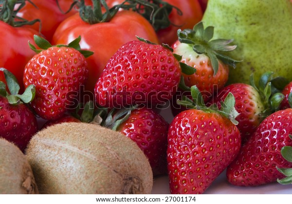 Shot of strawberries amongst other fruits and vegetables.