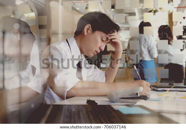 Shot of stressed asian business man in the office.