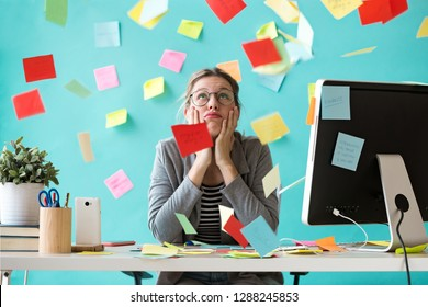 Shot of stressed young business woman looking up surrounded by notes in the office.