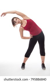 shot in the studio of young fitness woman standing stretching her arms and body